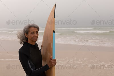 Front view of senior female surfer with surfboard standing on the beach