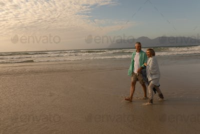 Side view of active senior couple walking hand in hand on the beach