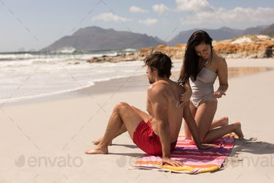 Beautiful happy young woman applying sunscreen lotion on mans back at beach in the sunshine