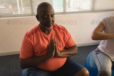 Front view of active senior men performing yoga, relaxing with ball exerciceat home