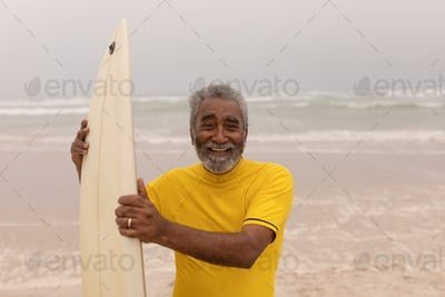 Front view of happy senior male surfer standing with surfboard and looking at camera on the beach