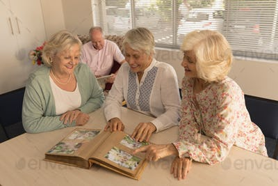 Front view of group of active senior women smiling and looking at photo album at nursing home