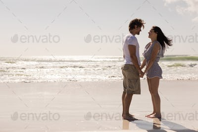 Side view of romantic young couple holding hands and looking each other on beach in the sunshine