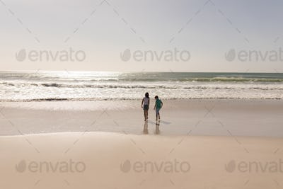 Rear view of siblings standing on beach in the sunshine