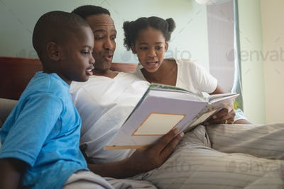Side view of African American father with his children reading storybook on bed in bedroom at home