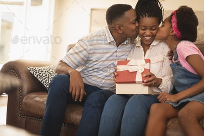 Portrait of happy African American father and daughter kissing mother on cheeks at home