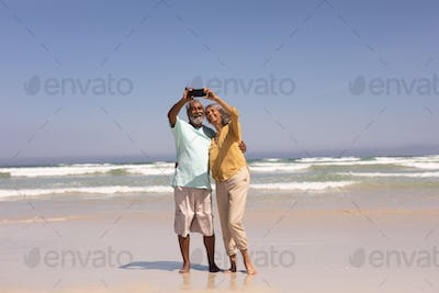 Front view of senior couple taking selfie with mobile phone on beach in the sunshine