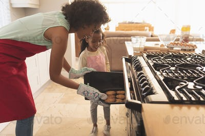Mother and daughter taking freshly baked cookies from the oven in the kitchen at home