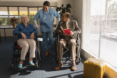 Front view of happy female doctor talking with disable senior couple at home