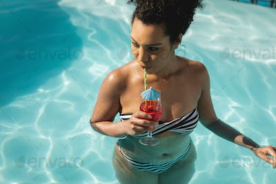 Front view of young mixed-race woman drinking cocktail in swimming pool on a sunny day
