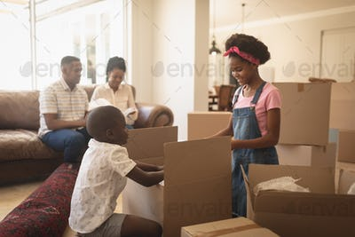 African American children unpacking their belongings and parents sitting on sofa at home
