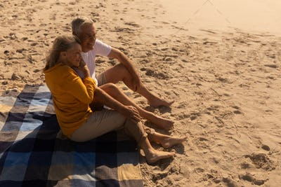 Side view of active senior couple relaxing on picnic blanket at beach