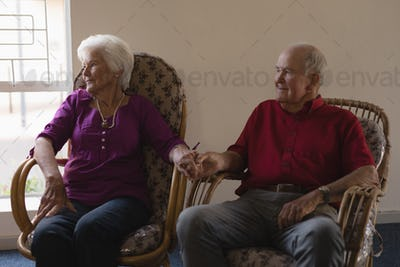 Front view of happy senior couple holding hands and looking away at nursing home
