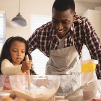 Front view of African American father and daughter baking cookies in kitchen at home
