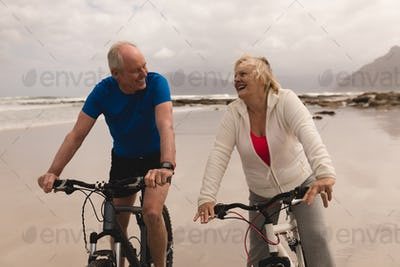 Front view of active senior couple riding a bicycle in a good mood on the beach