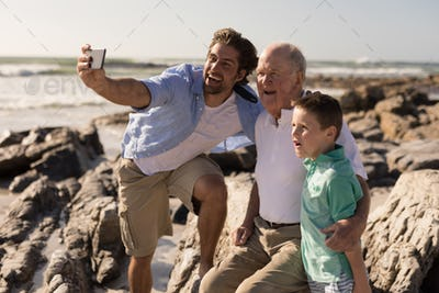 Front view of happy multi-generation family taking selfie with mobile phone on beach