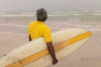 Rear view of senior male surfer with surfboard standing on the beach