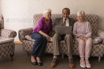 Front view of happy senior friends using laptop while sitting on sofa at home