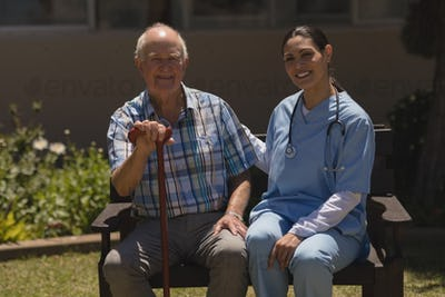 Front view of young female doctor and senior man looking at camera while sitting on bench in garden