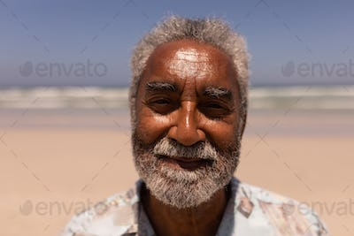 Close-up of senior black man looking at camera on beach in the sunshine