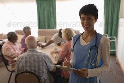 Female doctor holding clipboard and pen in with group of senior people playing card behind