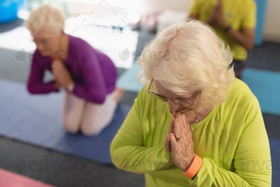 Front view of senior woman doing yoga on the foreground and her friend behind her in fitness studio