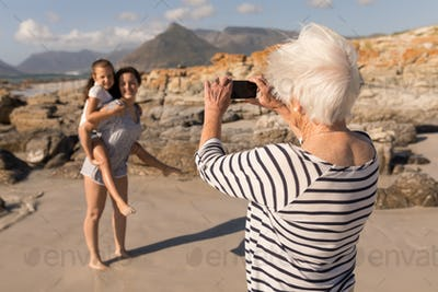 Rear view of senior woman clicking photo of her children with mobile phone on beach