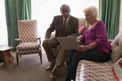 Front view of senior couple thoughtful and using laptop on sofa at home