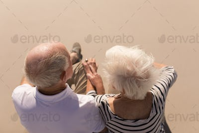 High angle view of romantic senior couple sitting on beach in the sunshine