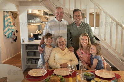 Front view of a multi-generation family posing together before having meal on dining table at home