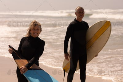 Front view of senior couple with surfboard standing on beach and looking at camera on a sunny day