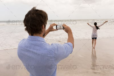 Rear view of man clicking photo of woman with mobile phone on the beach