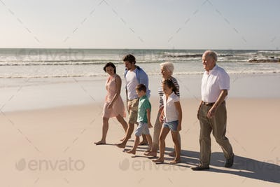 Side view of happy multi-generation family walking and having fun on beach in the sunshine