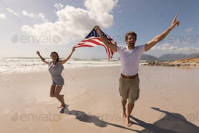 Happy young couple with arms outstretched holding american flag on beach in the sunshine