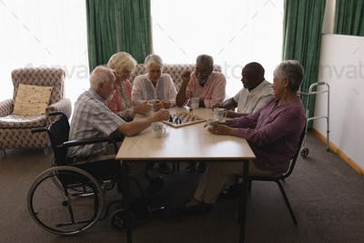 Front view of group of senior people playing chess on table in living room at home
