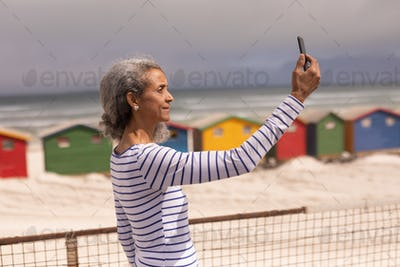 Side view of senior woman taking selfie with mobile phone on promenade at beach