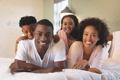 Front view of happy African American family lying on bed and looking at camera in a comfortable home