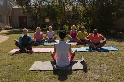 Front view of female trainer training senior people in performing yoga with yoga mat at park