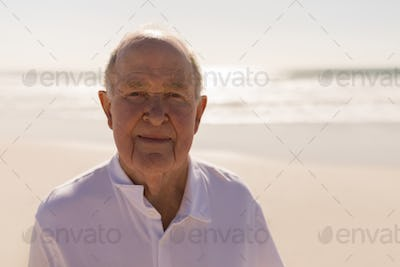 Front view of smiling senior man looking at camera on beach in the sunshine
