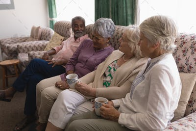 Front view of senior people having coffee on sofa in living room at home