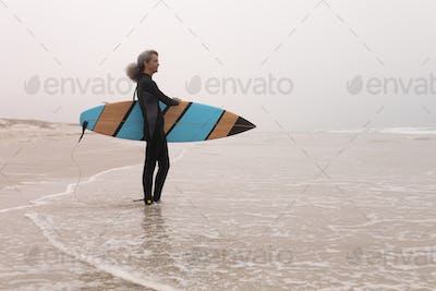 Side view of senior female surfer with surfboard standing on the beach