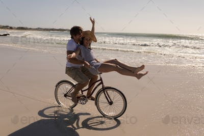 Side view of beautiful happy young woman sitting on man bicycle handlebars on beach in the sunshine