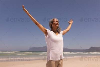 Low angle view of senior woman with arms outstretched standing on beach in the sunshine