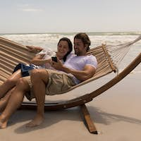 Front view of happy young couple relaxing on hammock and using mobile phone at beach in the sunshine