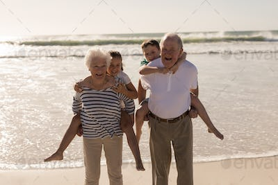 Front view of happy grandparents giving piggyback to grandchildren on beach in the sunshine