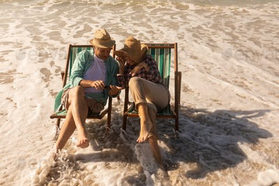 high angle view of active senior couple using mobile phone while relaxing on sun lounger at beach