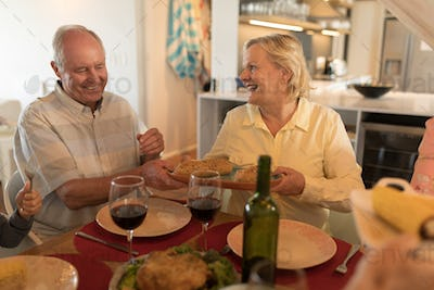 Side view of a senior couple interacting with each other on dining table at home
