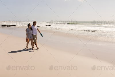 Front view of romantic young couple walking with beach footwear on beach in the sunshine