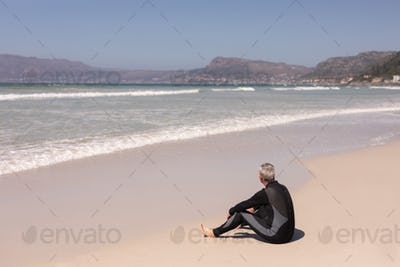 Rear view of thoughtful senior male surfer relaxing on the beach