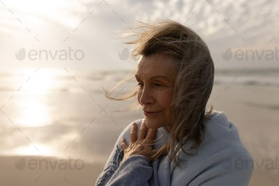 Closeup of thoughtful senior woman wrapped in a shawl standing on the beach